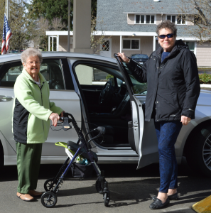 Photo shows an elderly woman with a walker standing in front of a car with the passenger door being held open by another woman who is a volunteer driver.