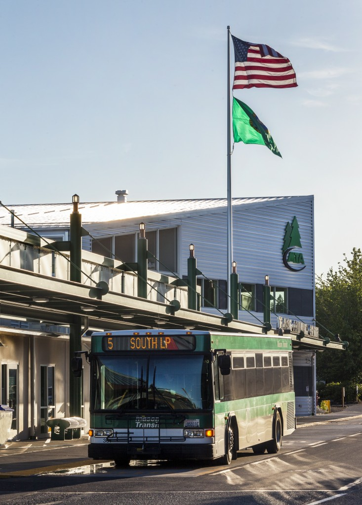 Photo of the front exterior of the Transit-Community Center building at sunset, with the American Flag and State Flag flying and a MTA bus parked in front.